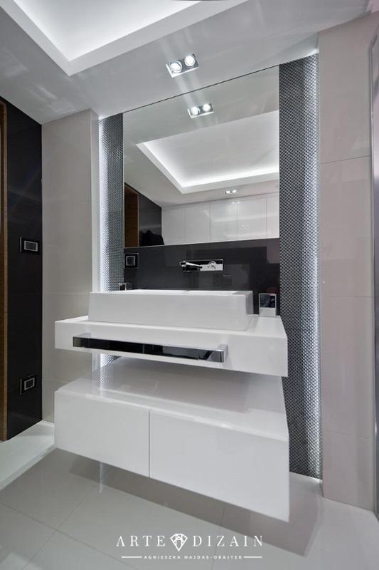 Kwadratowe lustro nad białą umywalką w łazience