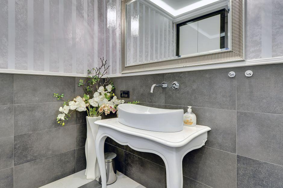 Konsola biała przyścienna pod umywalkę nablatową w aranżacji łazienki z lustrem o srebrnej ramie