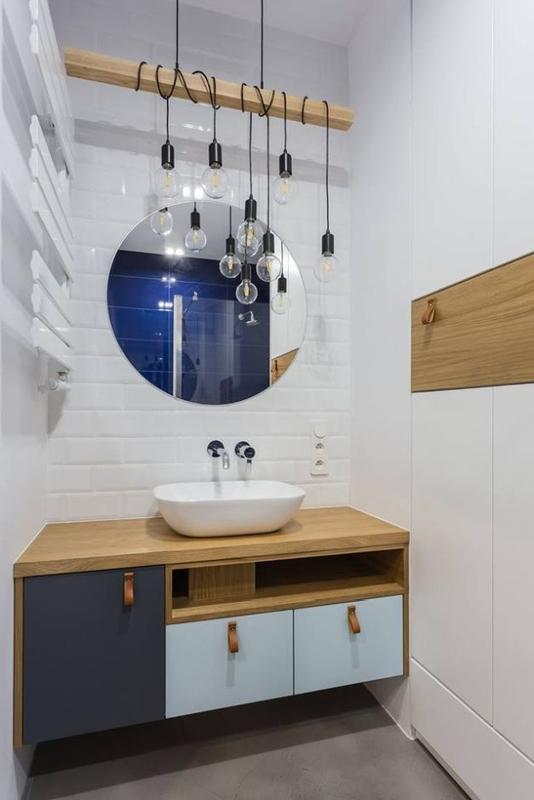 Kącik umywalkowy w łazience z dużym lustrem i lampą wiszącą
