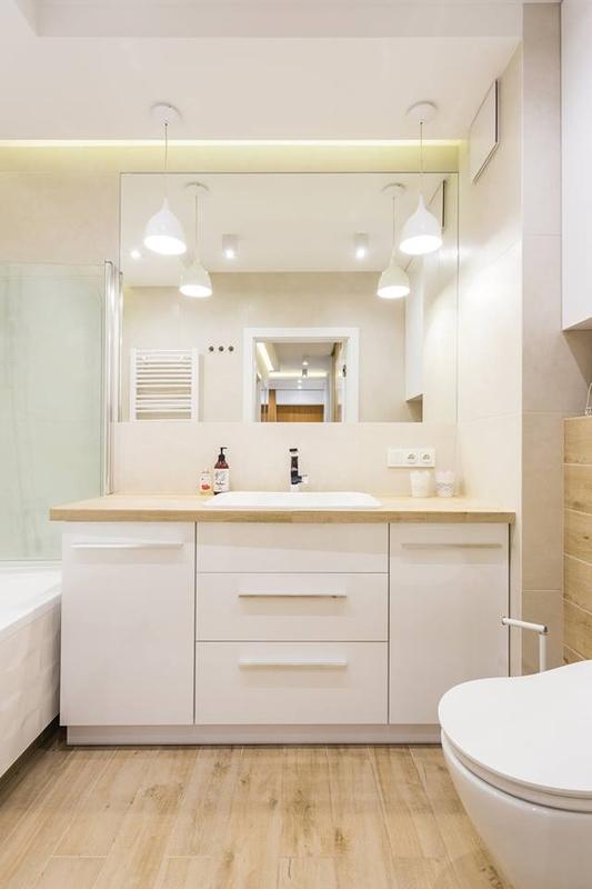 Jasna łazienka z lustrem nad białą umywalką