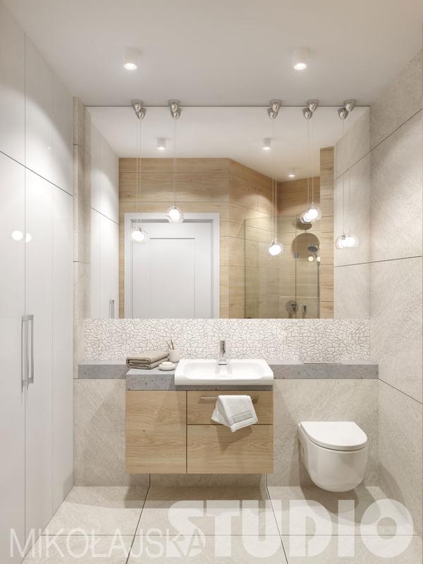 Jasna łazienka z dużym lustrem nad umywalką