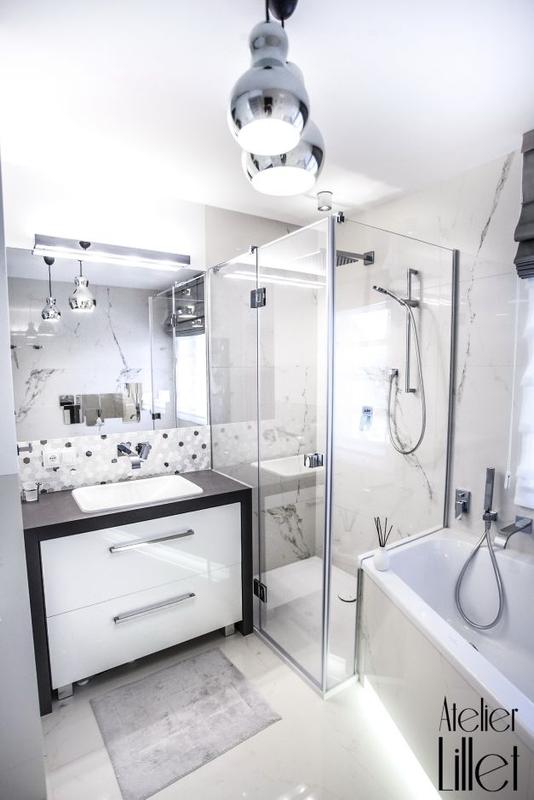 Jasna łazienka z chromowanymi dodatkami i lustrem nad umywalką