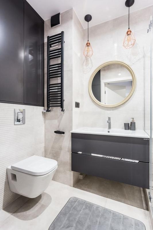 Industrialne lampy wiszące w łazience z okrągłym lustrem