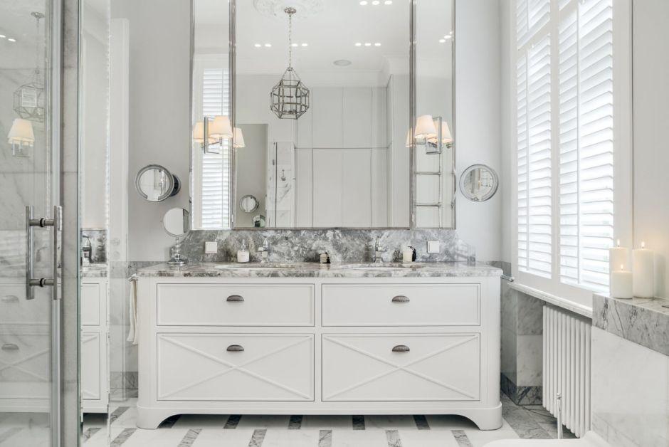 Dwie umywalki podblatowe oraz duże lustro w aranżacji łazienki z marmurem