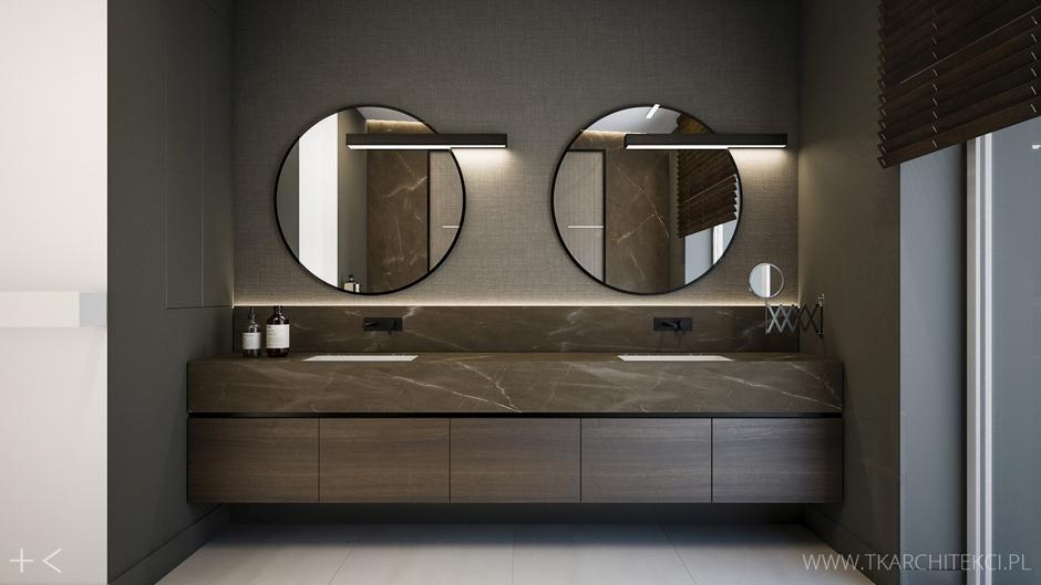 Dwa okrągłe lustra z czarnymi ramami w ciemnej łazience