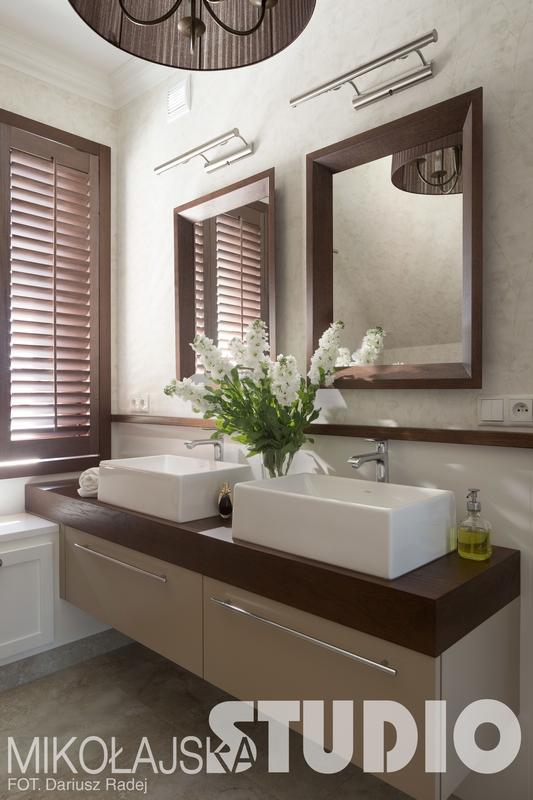 Dwa kwadratowe lustra w drewnianych ramach w łazience w brązowych odcieniach