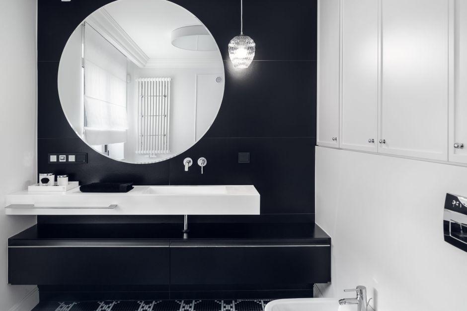 Duże okrągłe lustro w biało-czarnej łazience