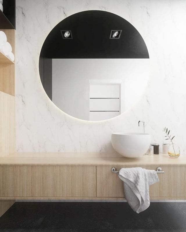 Duże okrągłe lustro nad umywalką
