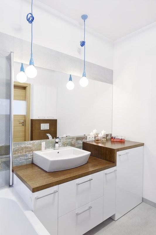Duże lustro w łazience z drewnianym blatem pod umywalkę