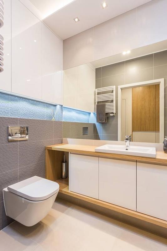 Duże lustro w łazience z płytkami strukturalnymi