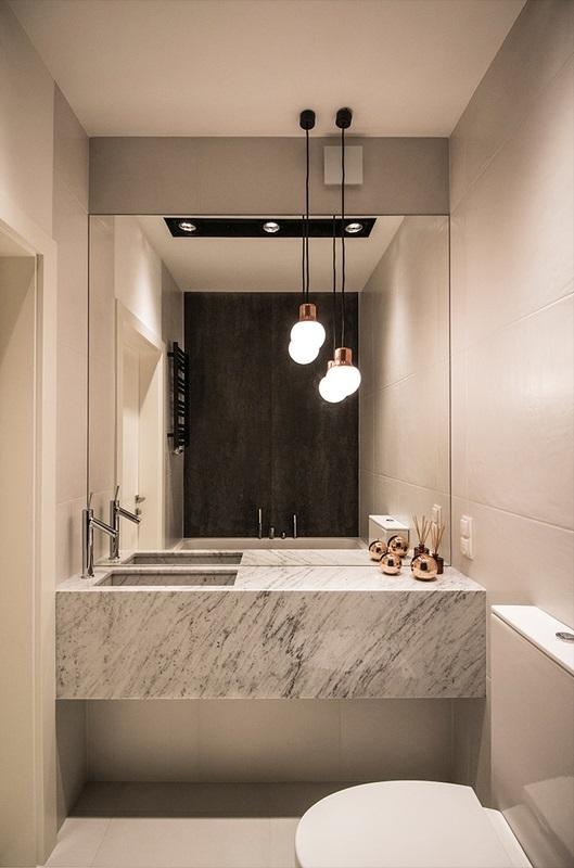 Duże lustro w łazience z marmurową umywalką