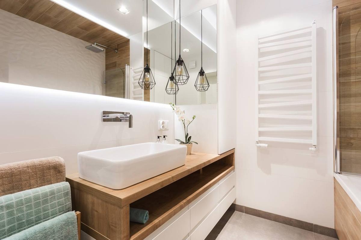 Duże lustro w łazience z industrialnym oświetleniem