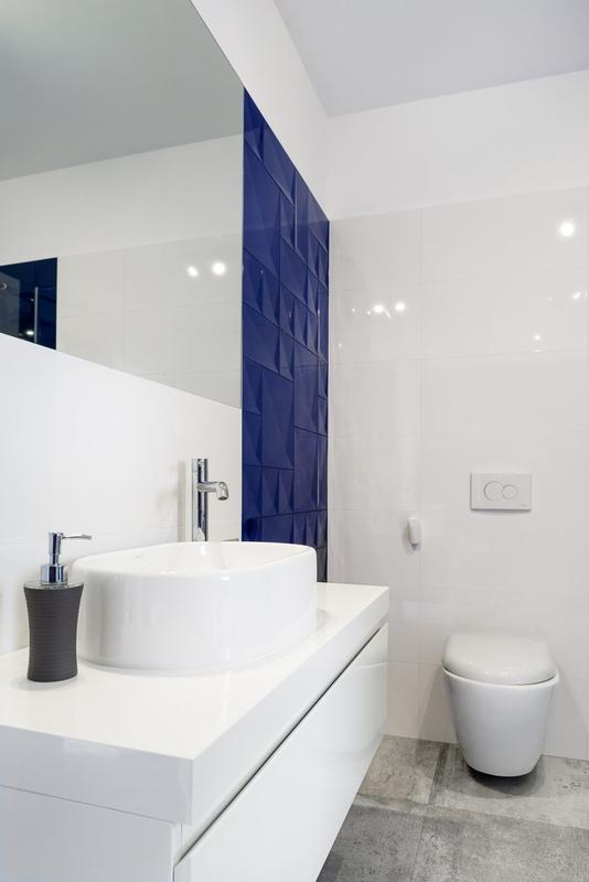 Duże lustro w łazience z granatowymi płytkami