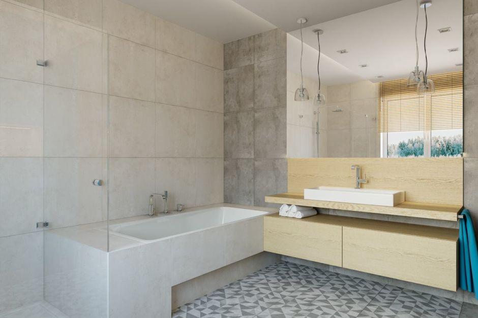 Duże lustro w łazience z betonem na ścianie