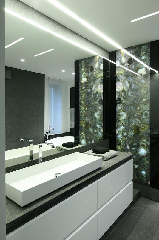 Duże lustro w łazience nad białą umywalką