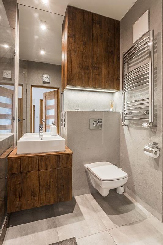 Duże lustro pokrywające ściane w małej łazience z drewnem