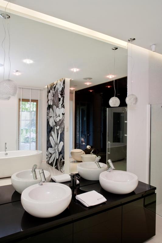 Duże lustro pokrywające ścianę w łazience z wanną wolnostojącą