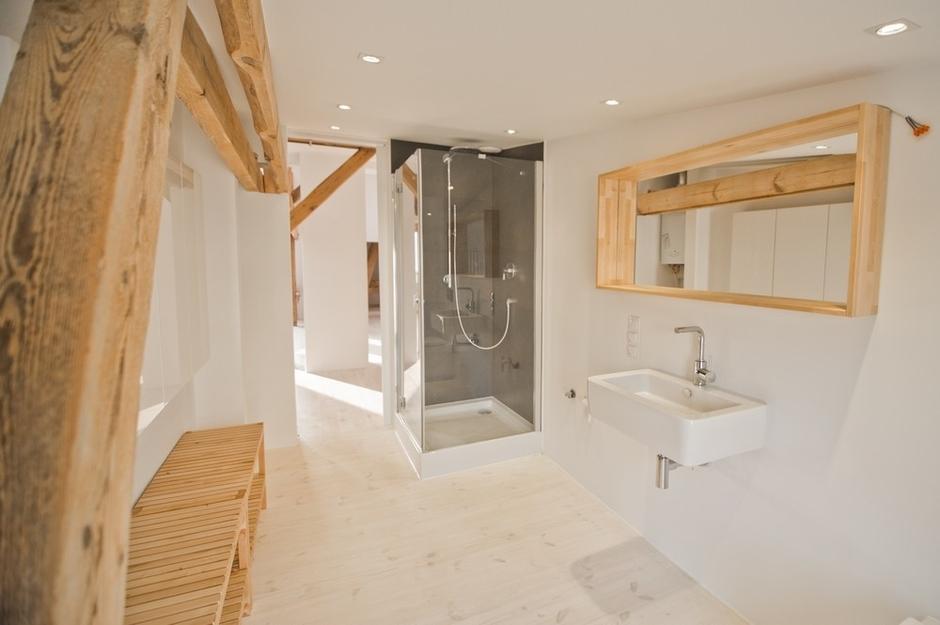 Duże lustro o drewnianej ramie w łazience z prysznicem