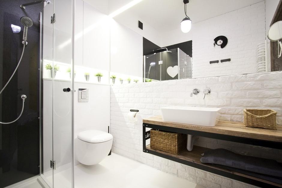 Duże lustro na ścianie w łazience z białą cegłą