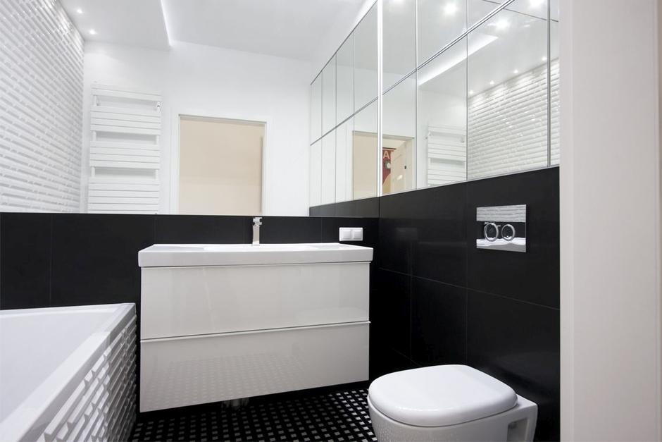 Duże lustro na ścianie w łazience w kolorach bieli i czerni