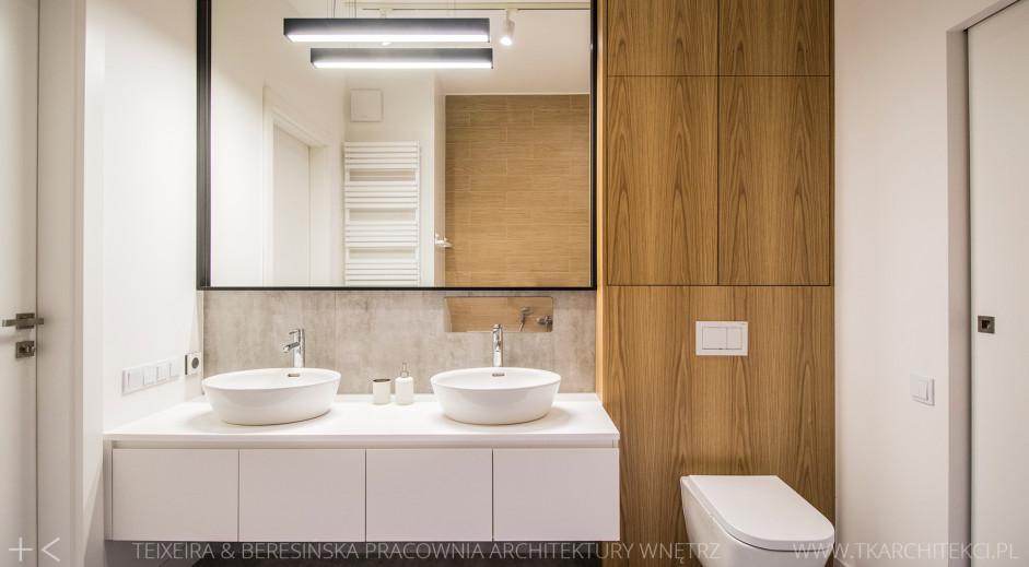 Duże kwadratowe lustro z czarna ramą w łazience z drewnem