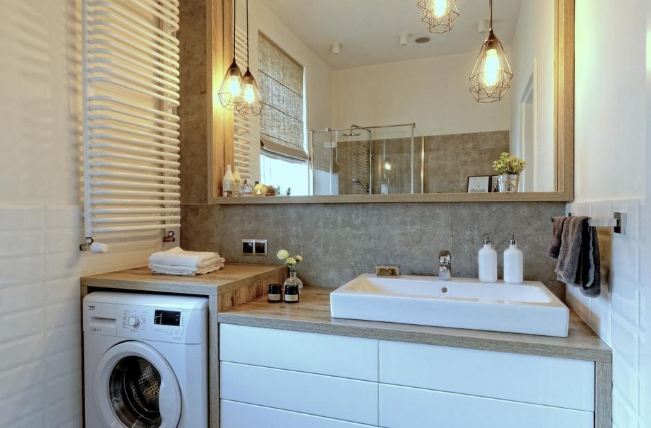Drewniana rama lustra w łazience z industrialnym oświetleniem