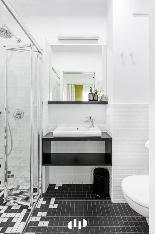 Biało-czarna łazienka z lustrem nad umywalką