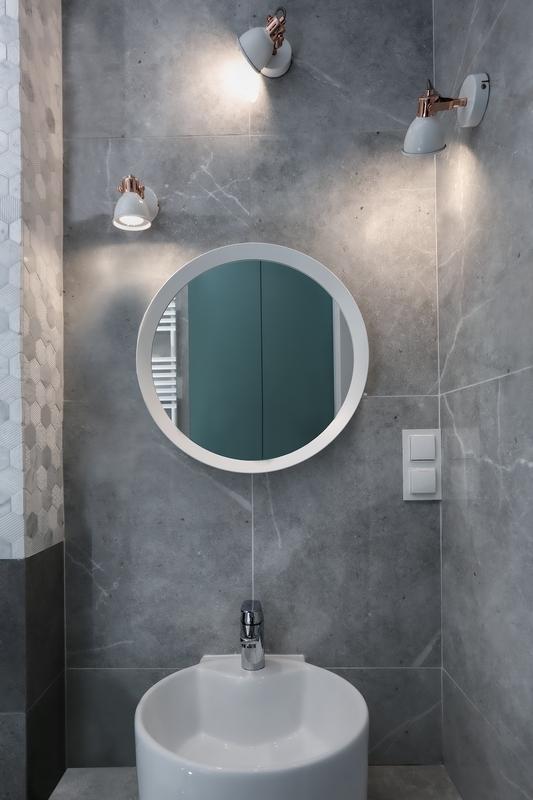 Biała rama okrągłego lustra w szarej łazience