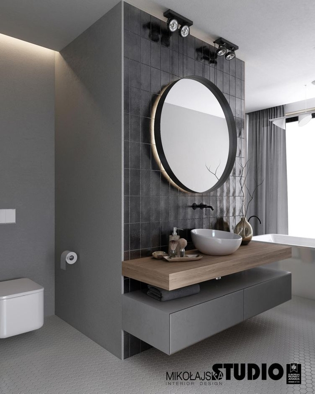 Szara łazienka z dużym okrągłym lustrem i małą umywalką nablatową