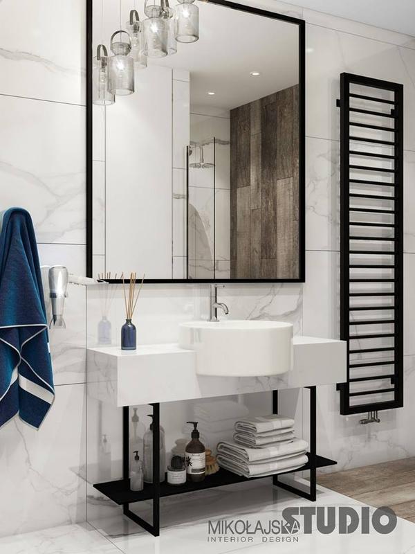 Duże lustro z czarną ramą w aranżacji łazienki