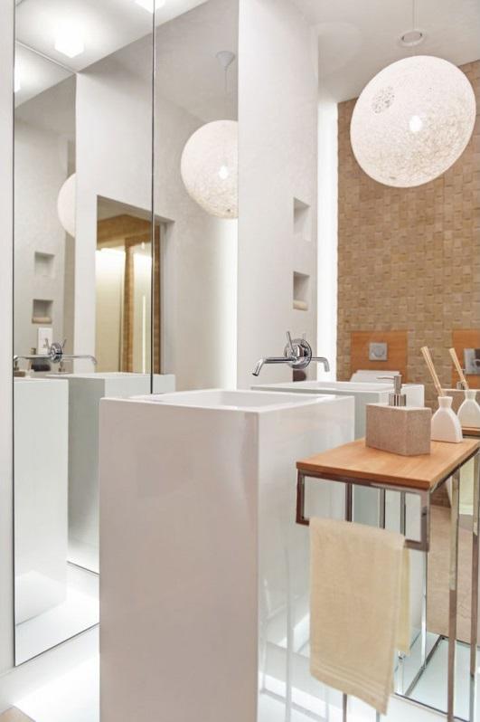 Duże lustro pokrywające ścianę w łazience z umywalką wolnostojącą