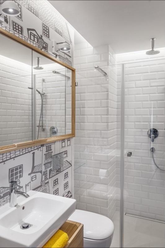 Drewniana szafka z lustrem nad umywalką w łazience z fototapetą