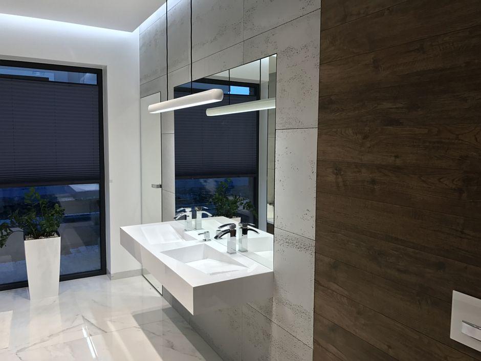Beton na ścianie w łazience z asymetryczną umywalką