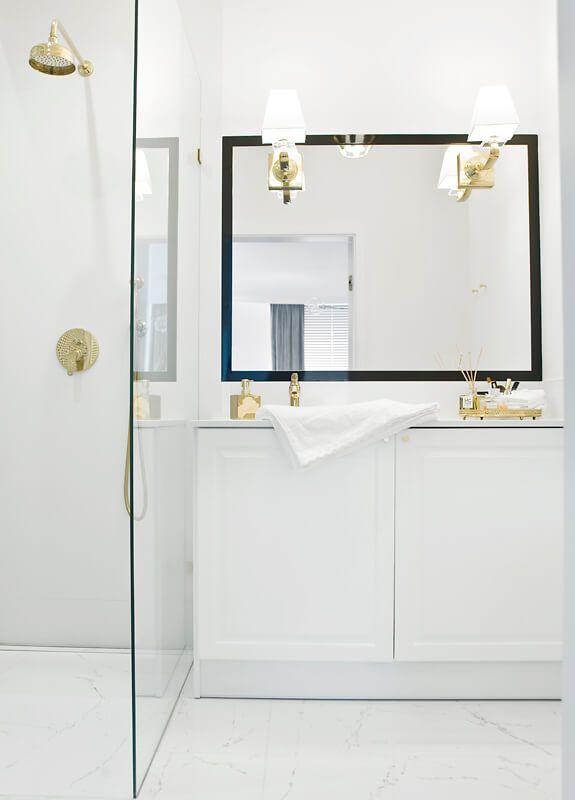 Lustro w czarnej ramie w łazience ze złotą armaturą