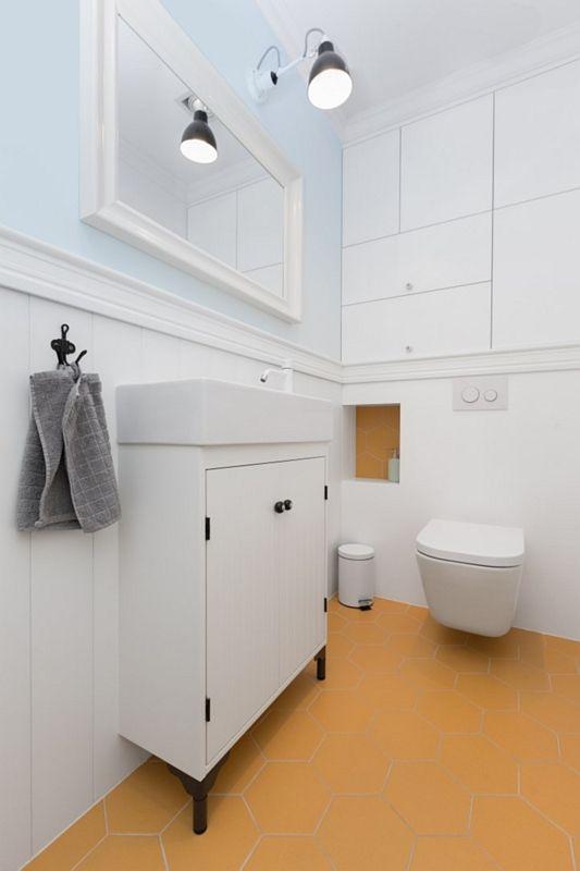 Prostokątne lustro w białej ramie w małej łazience