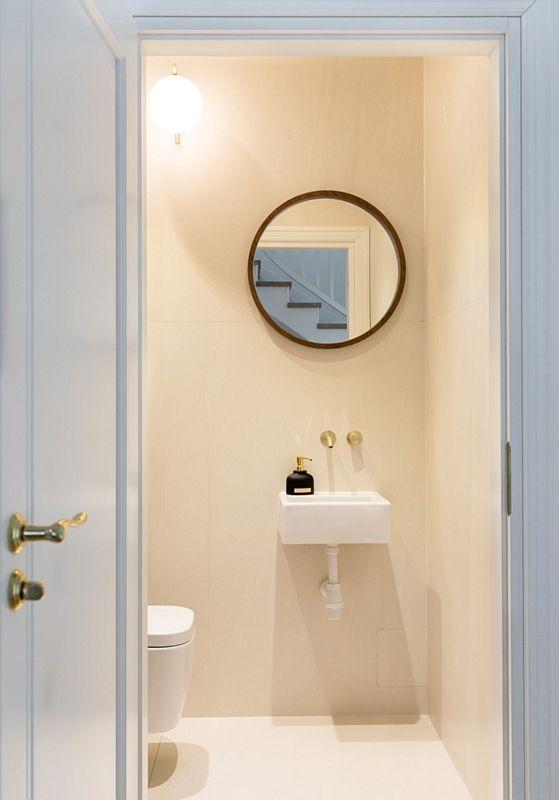 Małe okrągłe lustro w aranżacji jasnej łazienki