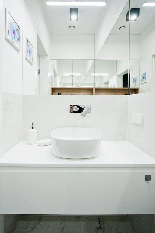 Duże lustro w łazience z owalną umywalką