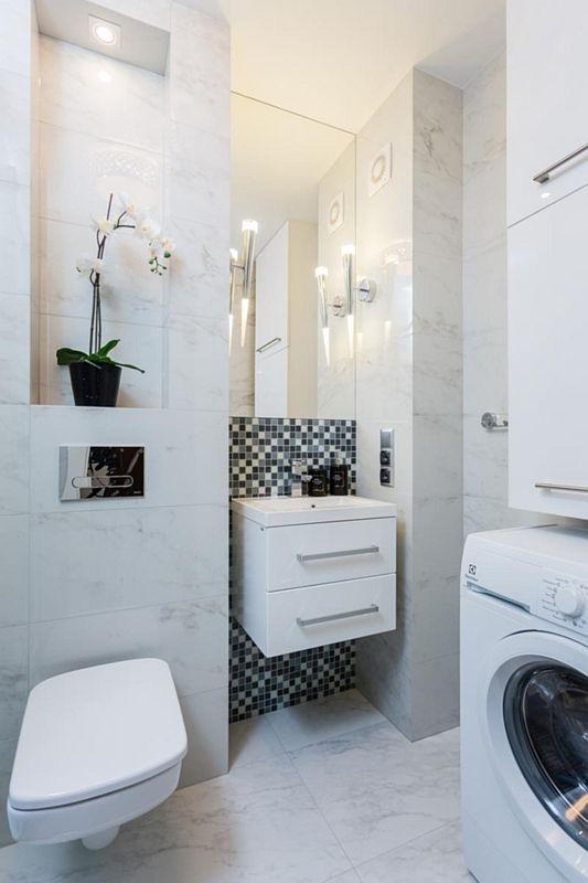 Prostokątne lustro nad małą umywalką