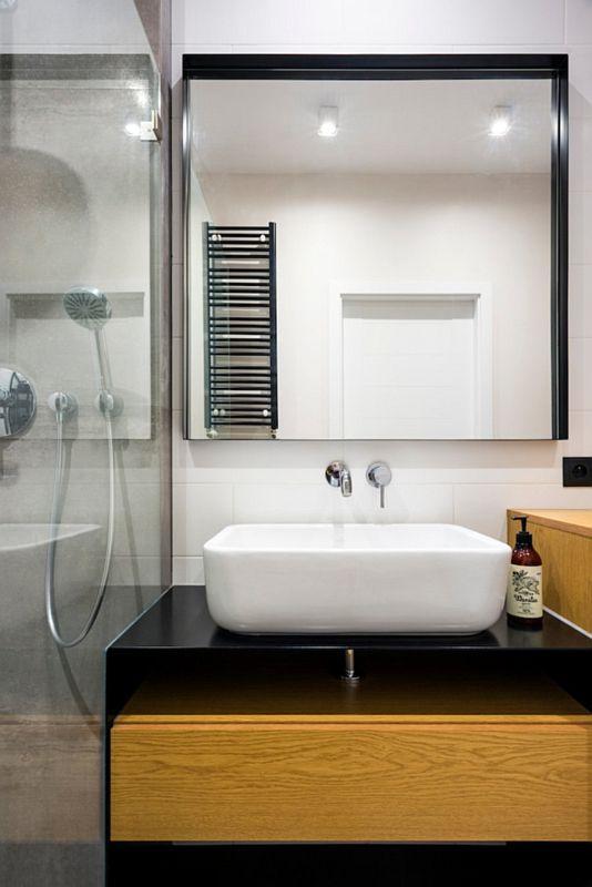 Lustro w ramie w łazience z drewnianą szafką