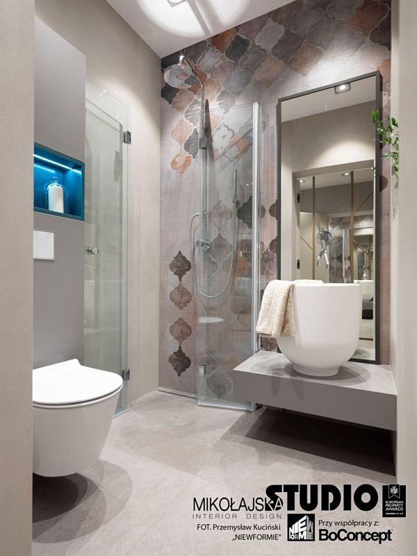 Duże lustro w szarej ramie w łazience z motywem arabeski na ścianie