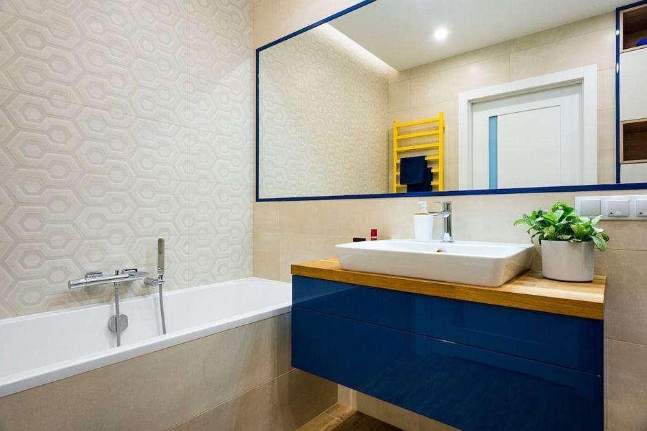 Lustro w niebieskiej ramie w łazience z płytkami strukturalnymi