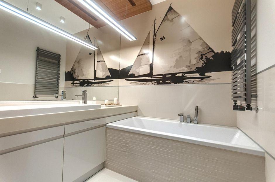Duże lustro w łazience z fototapetą i wanną w zabudowie