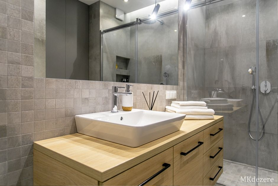 Lustro w łazience z drewnianą szafką pod umywalkę