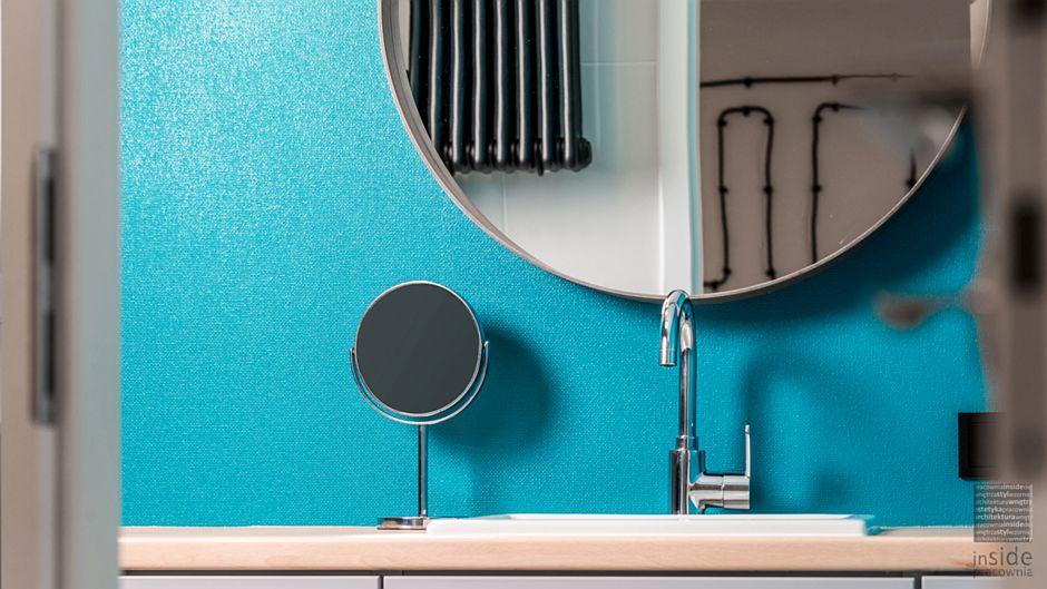 Okragłe lustro w łazience z niebieską ścianą