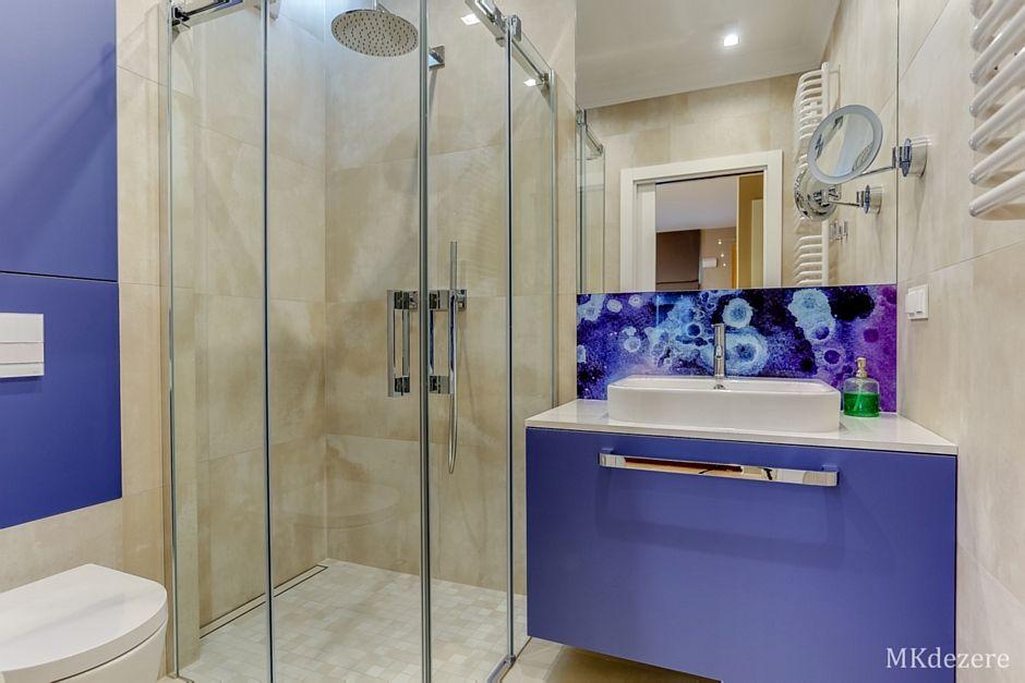 Lustro w łazience z niebieską szafką