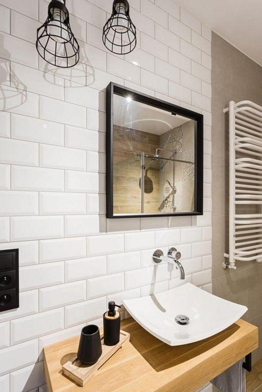 Lustro w czarnej ramie w aranżacji industrialnej łazienki