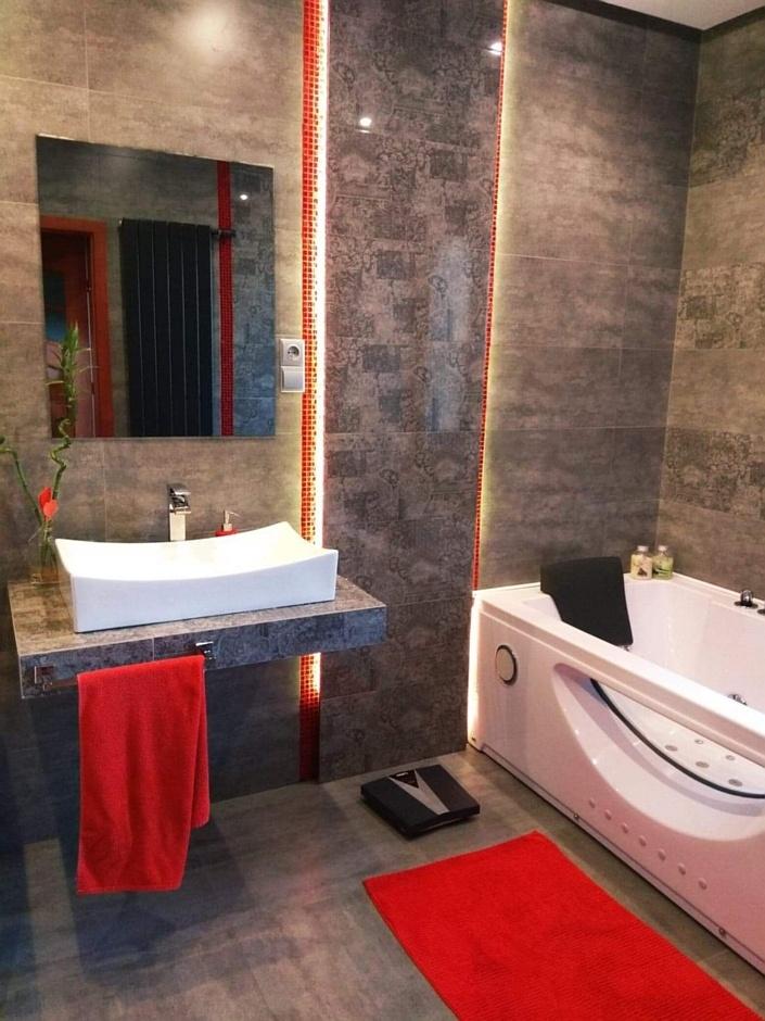 Czerwone elementy w łazience z wanną z hydromasażem