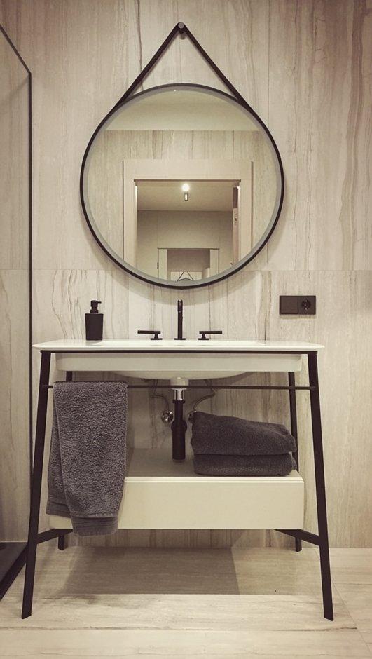 Okrągłe lustro na czarnym pasie w łazience