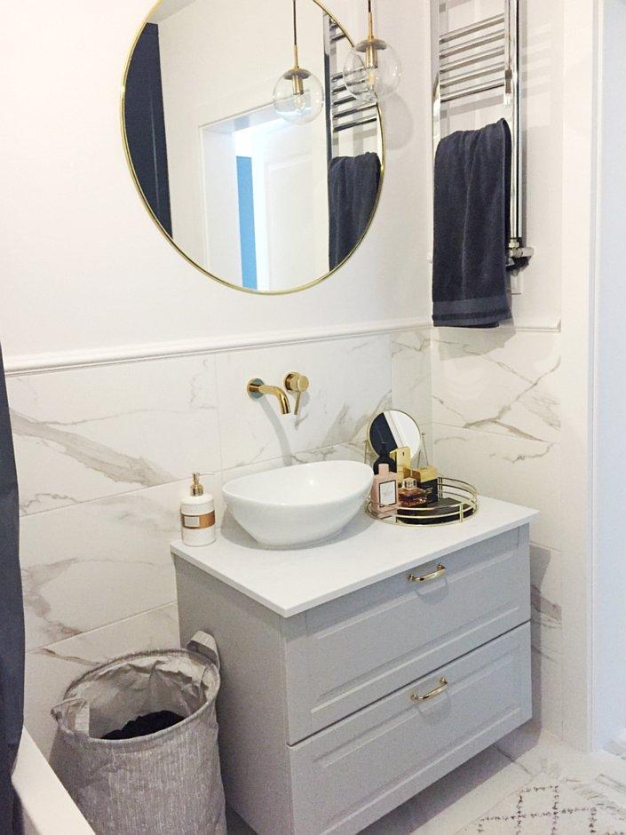 Lustro w złotej ramie nad szarą szafką pod umywalkę