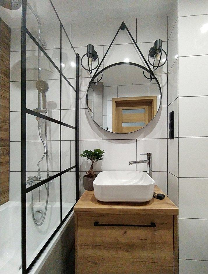 Okrągłe lustro na pasku w czarnej ramie nad umywalką w łazience